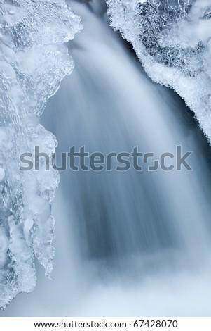 Winter waterfall framed by ice, Orangeville Creek, Michigan, USA - stock photo