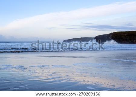 winter waves crashing onto the beach cliffs at ballybunion - stock photo