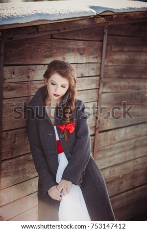 Winter wedding. Portrait of a bride in a white light dress and a gray coat. A red ribbon is woven into the braid. Wooden background. Red lips.