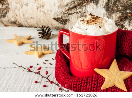 Winter whipped cream hot coffee in a red mug with star shaped cookies and warm scarf - rural still life - stock photo