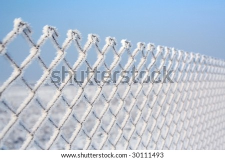 winter - wire fence covered by white frost - stock photo