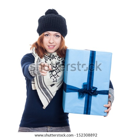 Winter woman holding big present and pointing at you, isolated on white background. - stock photo