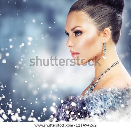 Winter Woman in Luxury Fur Coat.Beauty Christmas Girl Portrait. Fur Fashion. Snow. Jewelry - stock photo