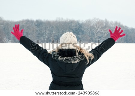 winter woman in snow showing her back and facing forest with hands raised high above, copy space outside on cold winter day.Portrait of happy joyful female model with pink gloves and hat in first snow - stock photo