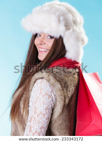 Winter woman in warm clothes fur cap with red paper shopping bag on blue. Girl buying. Sale and retail.