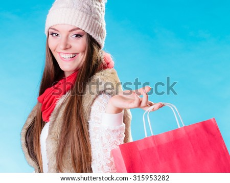 Winter woman in warm clothes with red paper shopping bag on blue. Happy girl buying. Sale and retail.