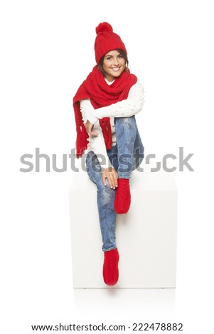 Winter woman wearing knitted warm red scarf, hat and socks sitting on blank billboard placard sign.