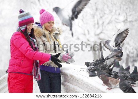 winter women give food to the pigeon - stock photo