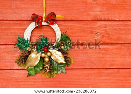 Winter wreath decoration hanging on a red wooden door background with free space for text and titles on the right side. - stock photo