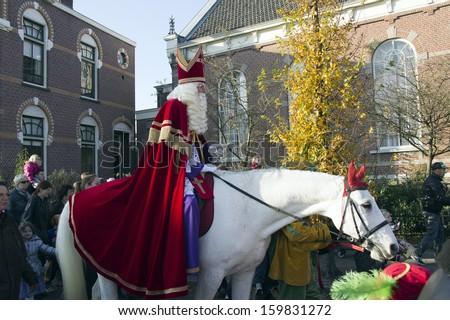WINTERSWIJK, HOLLAND- 12 NOVEMBER 2011: Santa Claus on his horse on Santa Claus parade on 12 November  2011 in Winterswijk, Holland. - stock photo