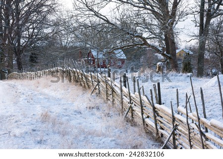 Wintry landscape in Smaland, Sweden, with typical wooden fence and wooden farm houses in the background - stock photo