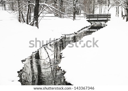 wintry winding creek, little bridge and snow covered landscape - stock photo