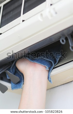 Wiping the inner part of an air-conditioner - stock photo
