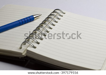 Wire-bound notebook; spiral-bound open notebook with pen; differential focus  - stock photo
