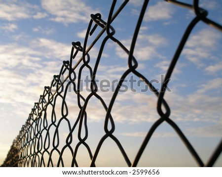 wire fence close up with sky - stock photo