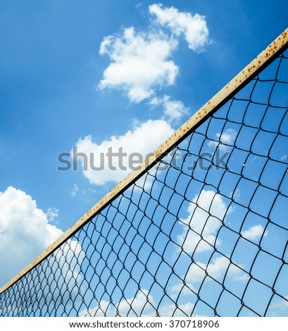 Wire mesh fence against blue sky - stock photo