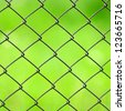 Wire Mesh Fence Close-Up on Green Background - stock photo
