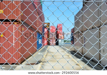 Wire mesh fence enclosing the container yard - stock photo