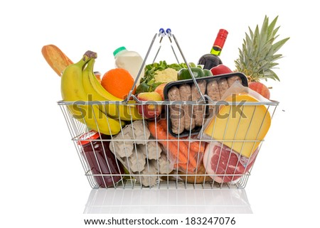 Wire shopping basket full of groceries including fresh fruit, vegetables, milk, wine, meat and dairy products. Isolated on a white background. - stock photo