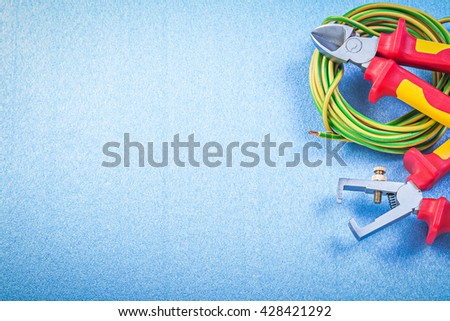 Wire stripper pliers electric cable nippers on blue background electricity concept. - stock photo