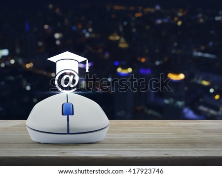 Wireless computer mouse with e-learning icon on wooden table in front of blurred light city tower, Study online concept - stock photo
