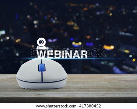 Wireless computer mouse with webinar icon on wooden table in front of blurred light city tower, Seminar online concept - stock photo