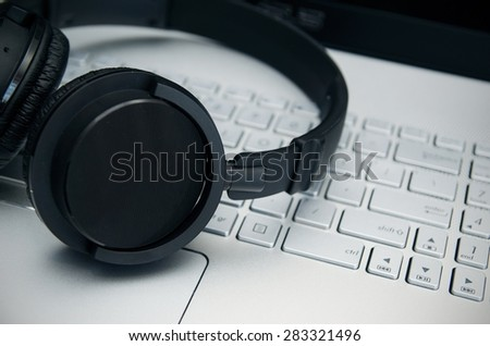 Wireless headphones on laptop keyboard. Music and gaming concept. - stock photo