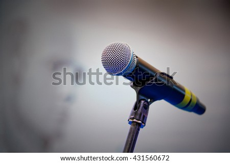 Wireless microphone on an empty stage with a blurred background.