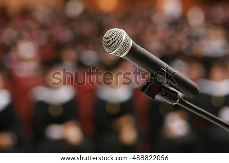 Wireless microphone on stage in auditorium with graduate student background.