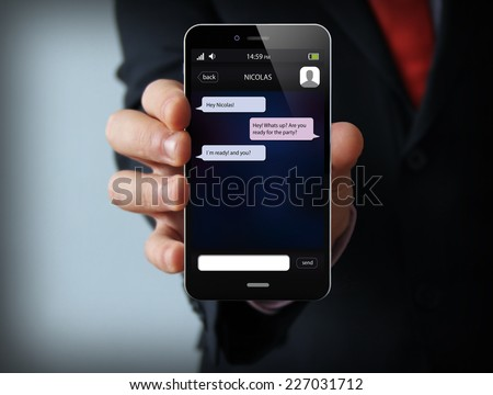 wireless, mobility and communications concept: businessman hand holding a phone with chat app on the screen