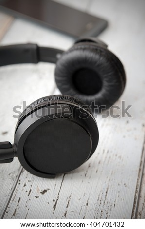 Wireless modern head phones and smart phone on wooden background - stock photo