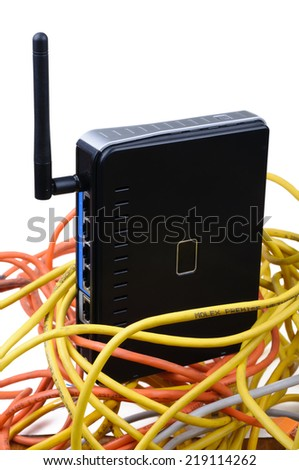 Wireless router among tangled network wires. Isolated on white background. - stock photo