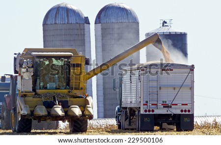 Wisconsin, USA - October 5, 2010:  Harvesting corn with combine iand unloading it into a silo - stock photo
