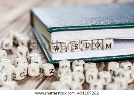 Wisdom word written on a wooden block in a book. On old wooden table.