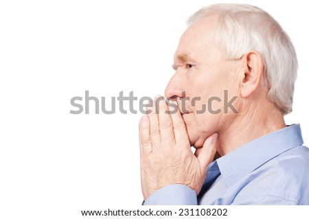Wise and confident. Side view of senior man shirt holding hands clasped and looking away while sitting in chair at his apartment - stock photo