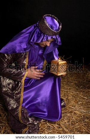 Wiseman from the east, bowing on bended knee and holding a gift of golden box filled with fine frankincense resin. - stock photo