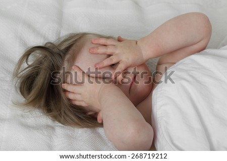 Wish to sleep - Infant baby in bed under blanket closes her eyes with hands - stock photo
