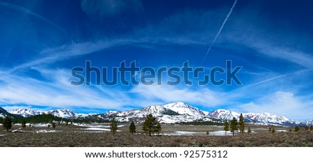 Wisps of cloud drift over snow-covered mountains east of Yosemite National Park in central California. - stock photo