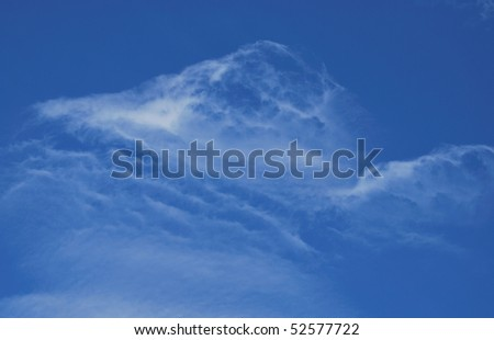 Wispy white clouds against a bright blue sky - stock photo