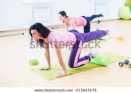 Wit women one leg extension kneeling kickbacks, exercise for lower back, hips and buttocks exercising at fitness club - stock photo