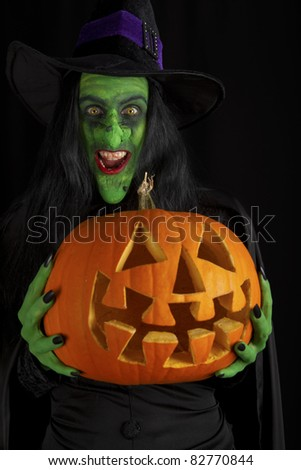 Witch and her pumpkin, black background. - stock photo