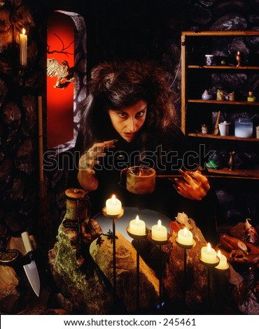 Witch at cauldron - stock photo