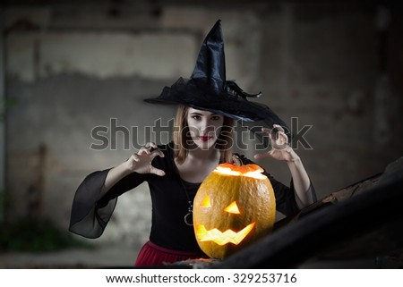 Witch casting her spells with pumpkin - stock photo