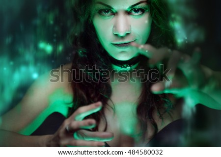 Witch creates magic. Beautiful and sexy woman with a mystical light