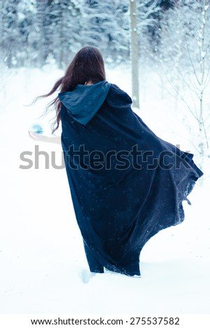 Witch in black cloak with magi? ball - stock photo