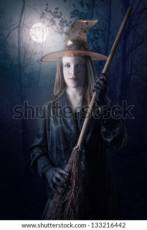 Witch in forest with full moon at night - stock photo