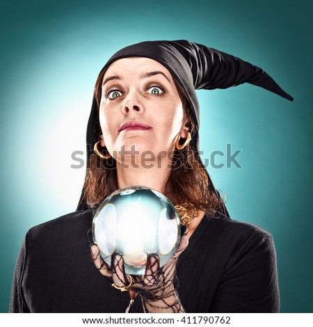 witch or sorceress with hat and crystal ball on green background - stock photo
