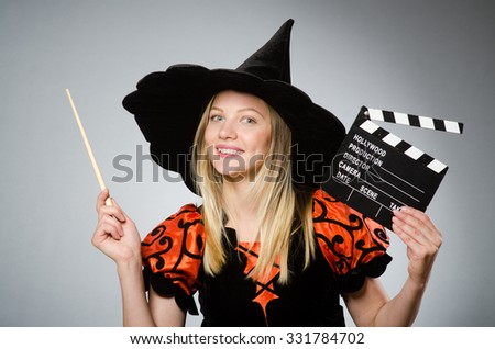 Witch with the movie clapboard  - stock photo