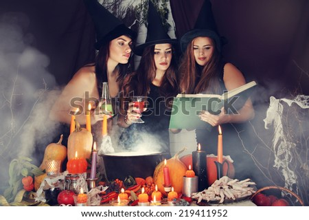 Witches look into the book of magical recipes - stock photo