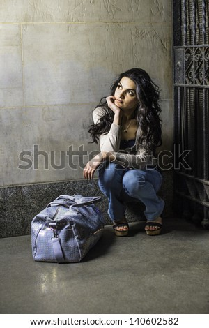 With a bag a young pretty woman is squatting in the front of a metal gate and waiting and thinking/Traveler